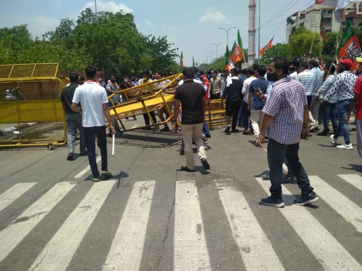 प्रदर्शनकारियों को रोकने के लिए लगाए गए बैरिकेट्स को गिराते कार्यकर्ता।