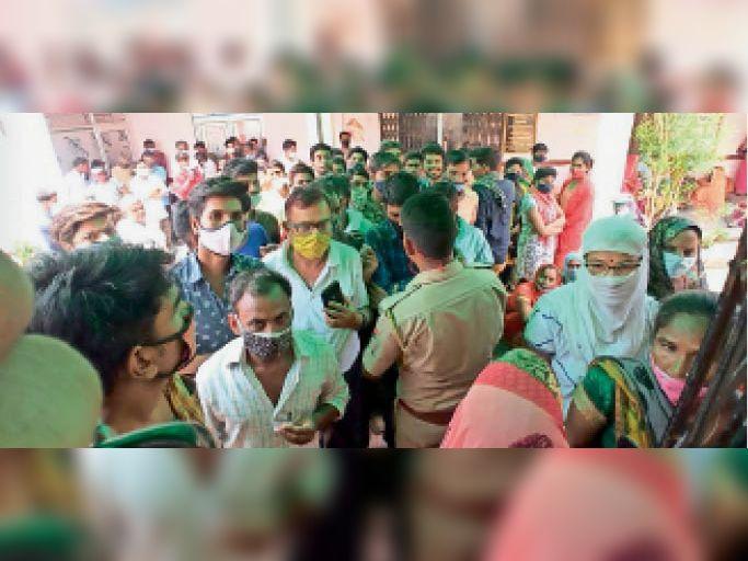 कवाई. कस्बे के अस्पताल में टीकाकरण शिविर में हुए हंगामे के दौरान लोगों से समझाइश करता पुलिसकर्मी। - Dainik Bhaskar