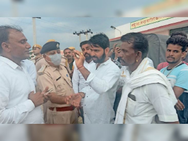 सारोलाकलां. बुधवार को विरोध-प्रदर्शन के दौरान समाज के लोगों से समझाइश करते पुलिस अधिकारी। - Dainik Bhaskar