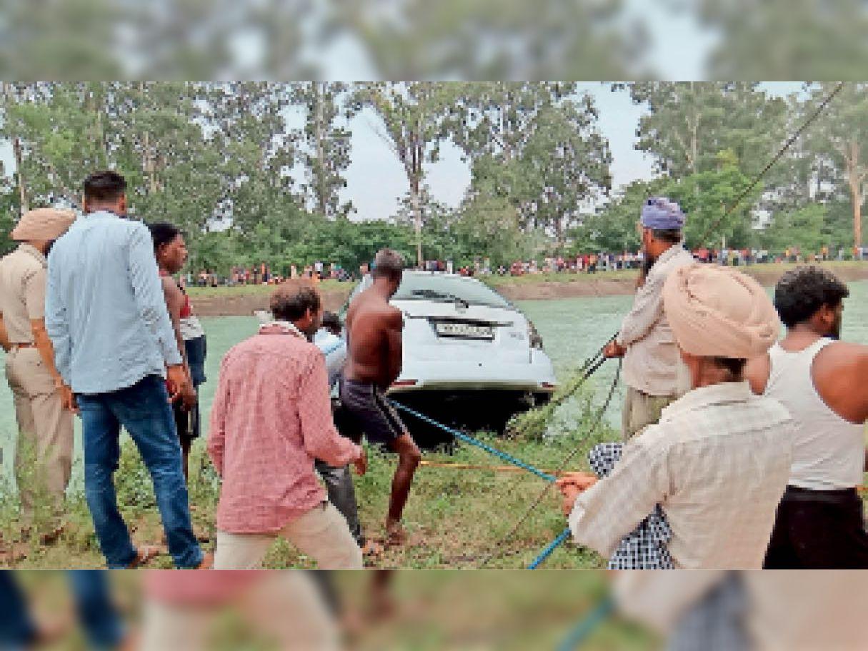 कार को बाहर निकालते हुए गोताखोर। - Dainik Bhaskar