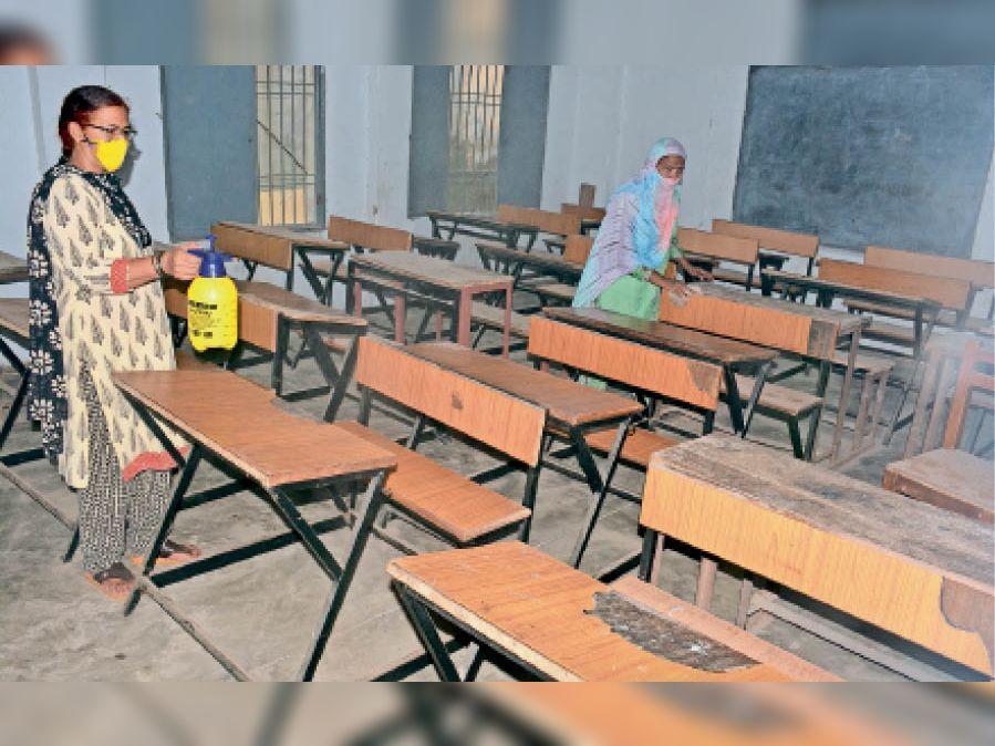 गांधी नगर के सीनियर सेकंडरी स्कूल में बैंच को सेनिटाइज करते हुए कर्मी। - Dainik Bhaskar