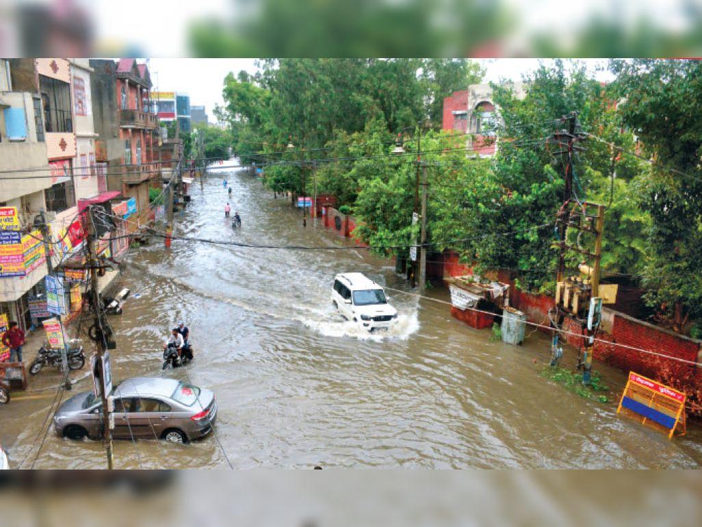 बारिश होने से तहसील रोड स्थित रेडक्रॉस भवन के पास शहर में भरे हुए बरसात के पानी से गुजरते वाहन। - Dainik Bhaskar
