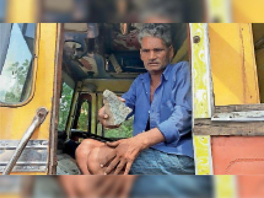ट्रक के अंदर फेंके पत्थर दिखाता पीड़ित ड्राइवर। - Dainik Bhaskar