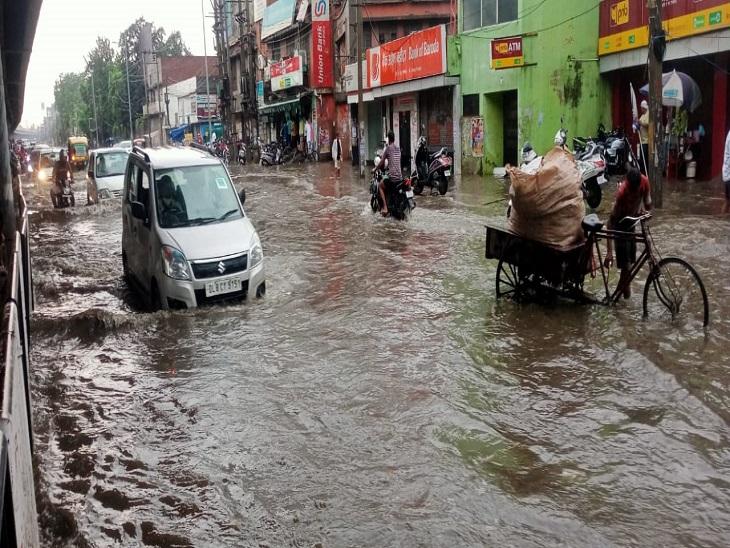 शहर की सड़कों पर घुटनों तक भरे पानी से गुजरते वाहन।