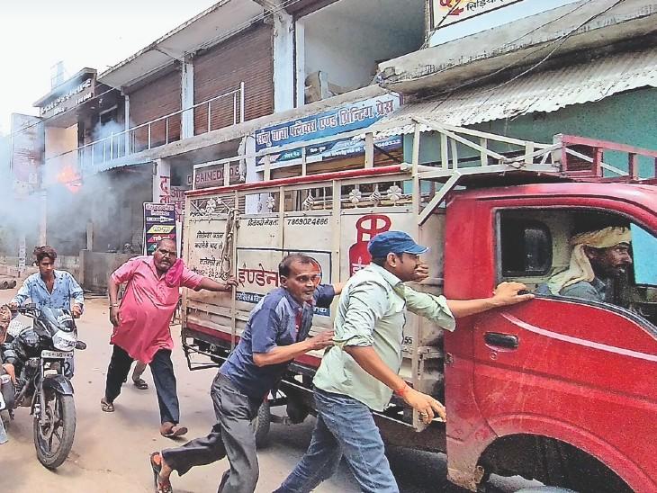 गैस सिलेंडर से भरी गाड़ी को हटाते लोग।