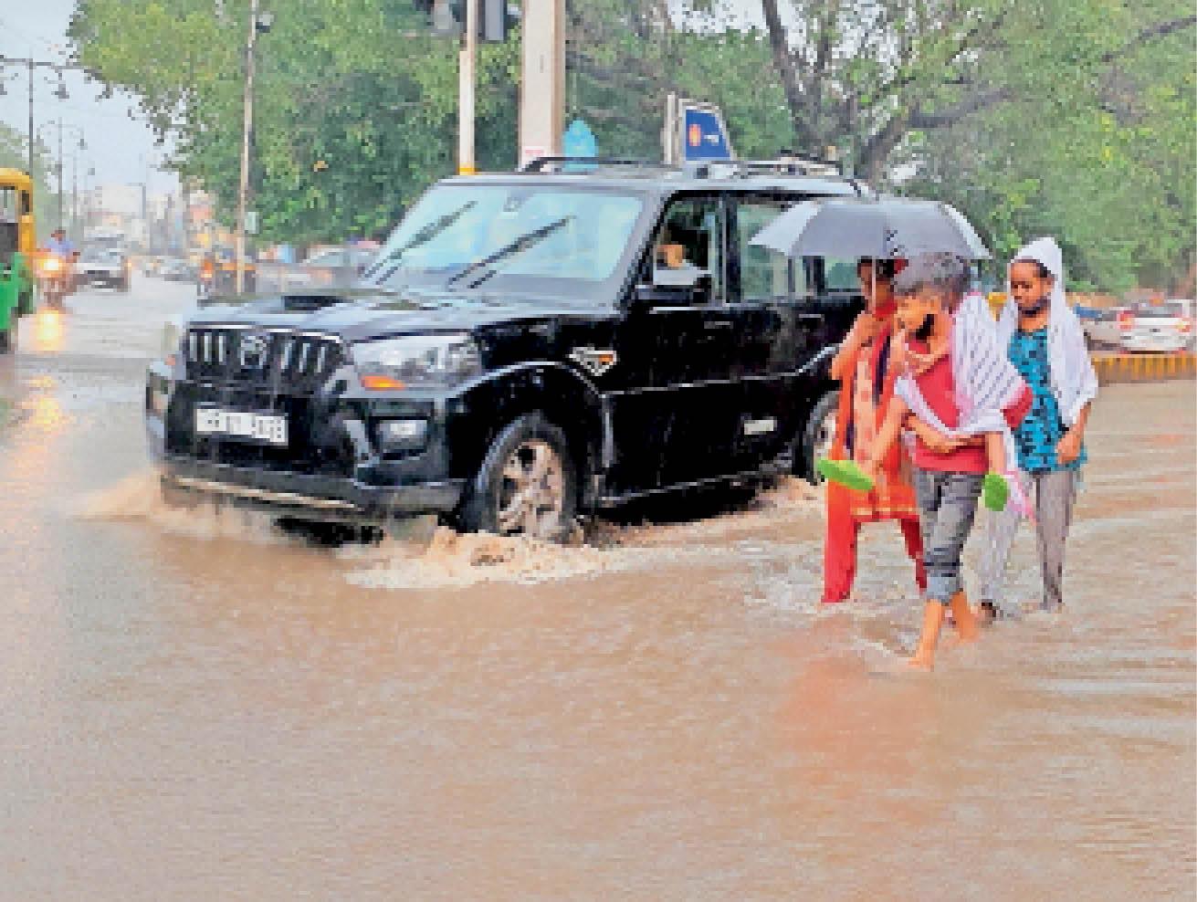 अग्रसेन चौक के निकट सड़क पर जाम पानी से निकलते वाहन व राहगीर। - Dainik Bhaskar