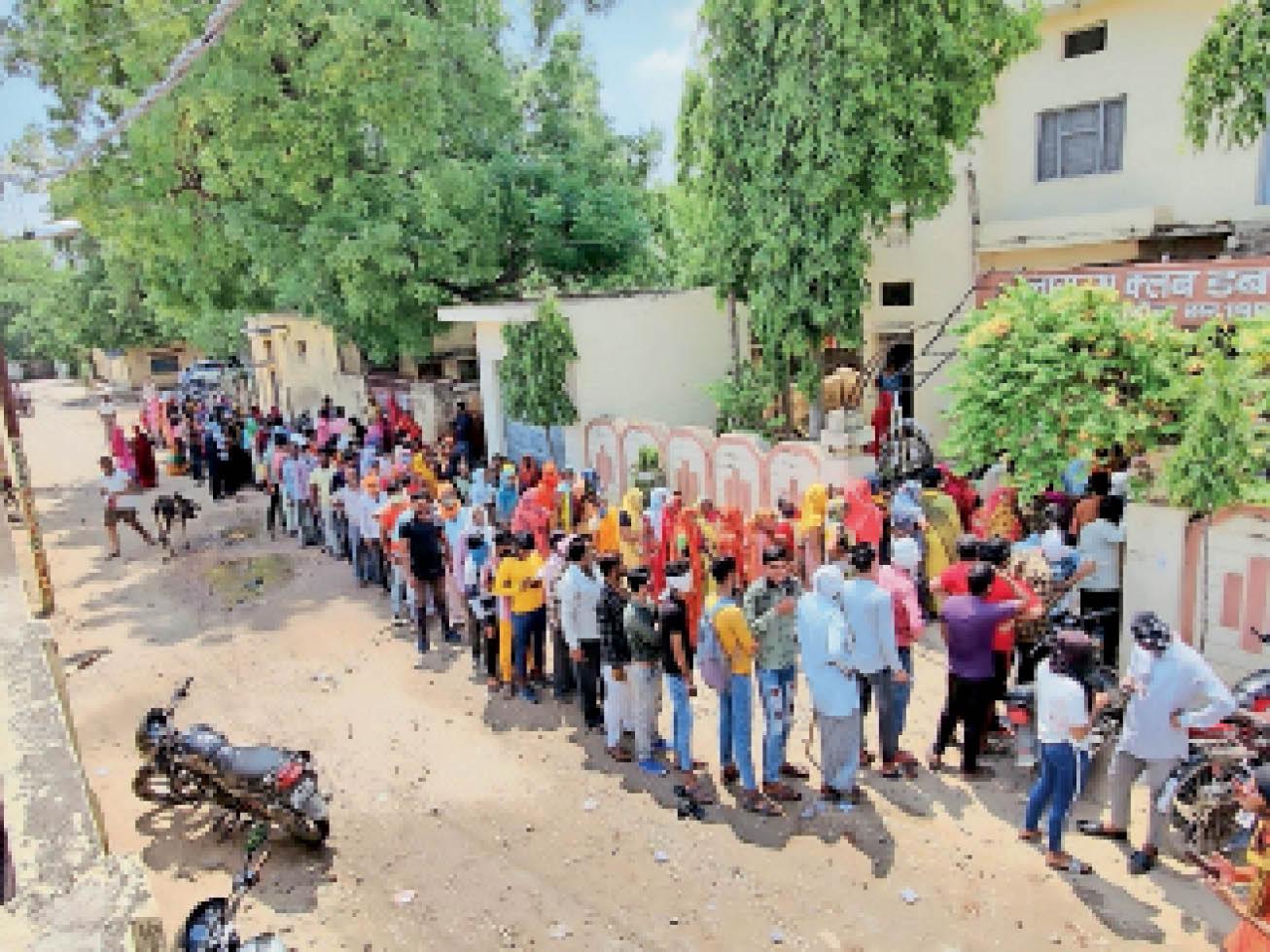 लायंस क्लब के अटेंडर हॉल में बने वैक्सीनेशन सेंटर पर सुबह छह बजे से ही लग गई लोगों की लंबी लाइन। - Dainik Bhaskar