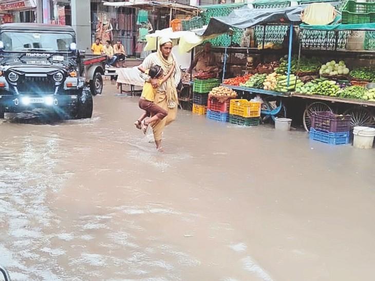 चिड़ावा. बुधवार दोपहर हुई बरसात के बाद पुरानी तहसील रोड पर भरे पानी से बचकर गुजरते राहगीर। - Dainik Bhaskar