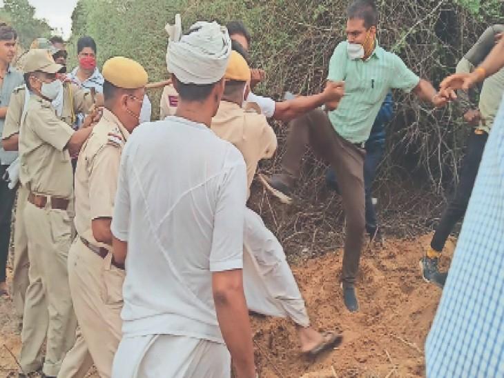 किसान की तरफ लात मारते हुए एसडीएम यादव, कार्य रूकवाने के लिए किसान इस तरह जेसीबी के आगे बैठ गए थे। - Dainik Bhaskar