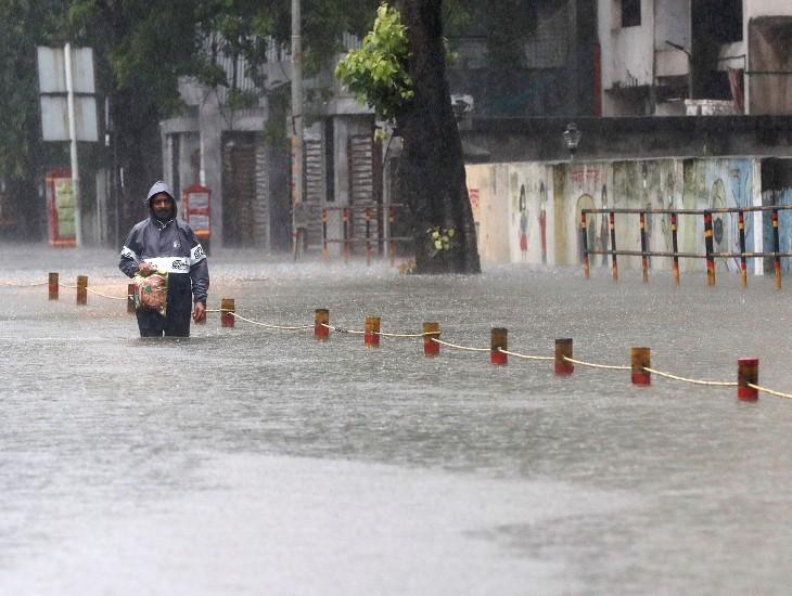 भारी बारिश के बीच मुंबई के सायन इलाके में बाजार से सामान लेकर जा रहा एक व्यक्ति