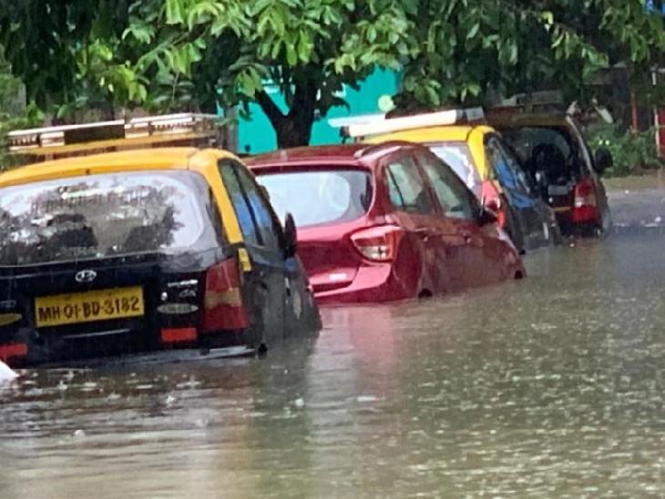 मुंबई के चूनाभट्टी इलाके में पानी में डूबी सड़क किनारे खड़ी कारें।