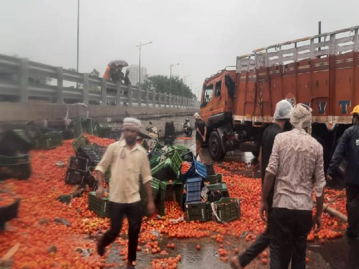 मुंबई के वेस्टर्न एक्सप्रेसवे पर भारी बारिश के बीच टमाटरों से भरा एक ट्रक पलट गया।