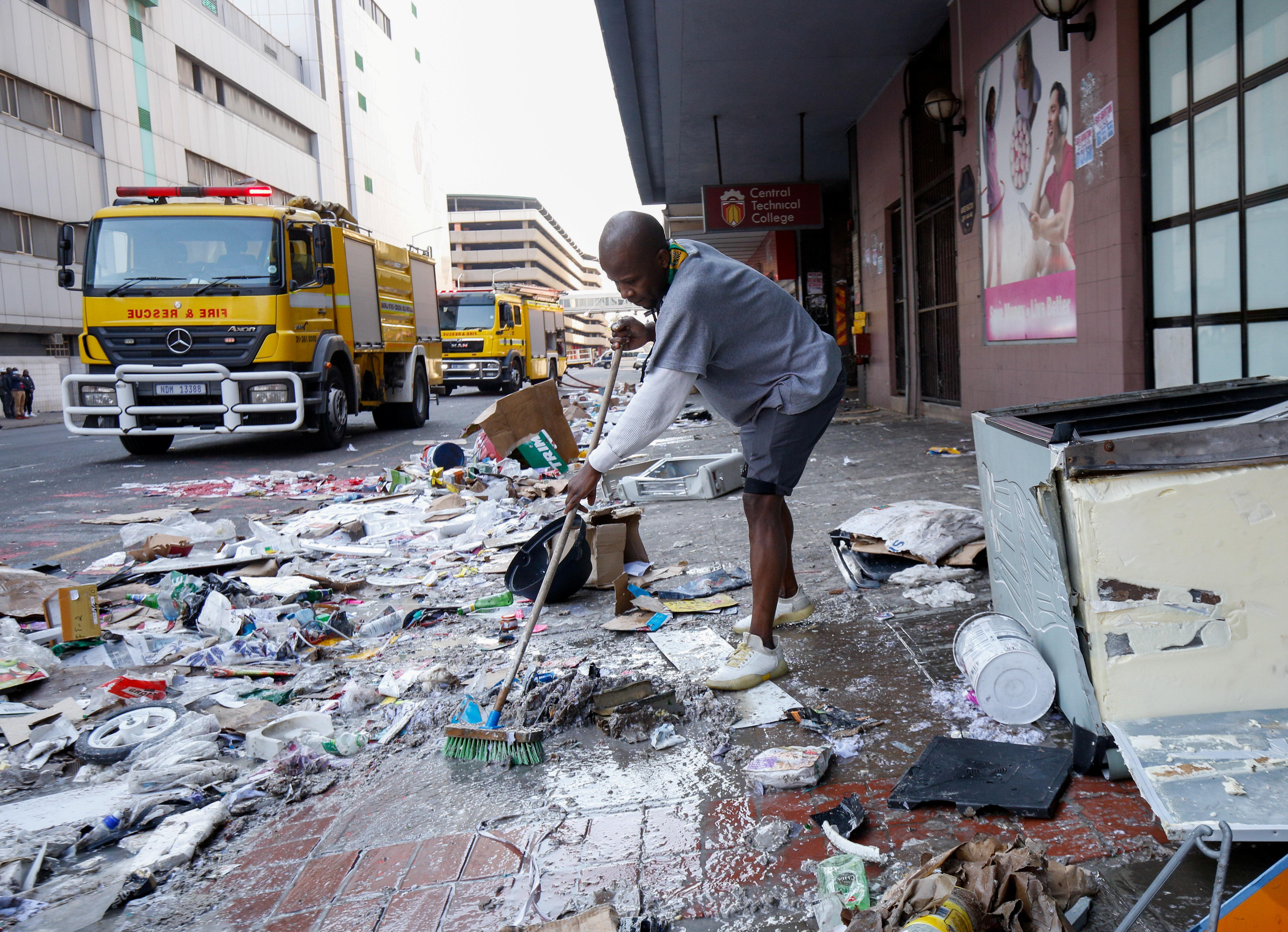 लूटपाट के बाद दुकान के सामने पड़े कचरे की सफाई करता युवक।