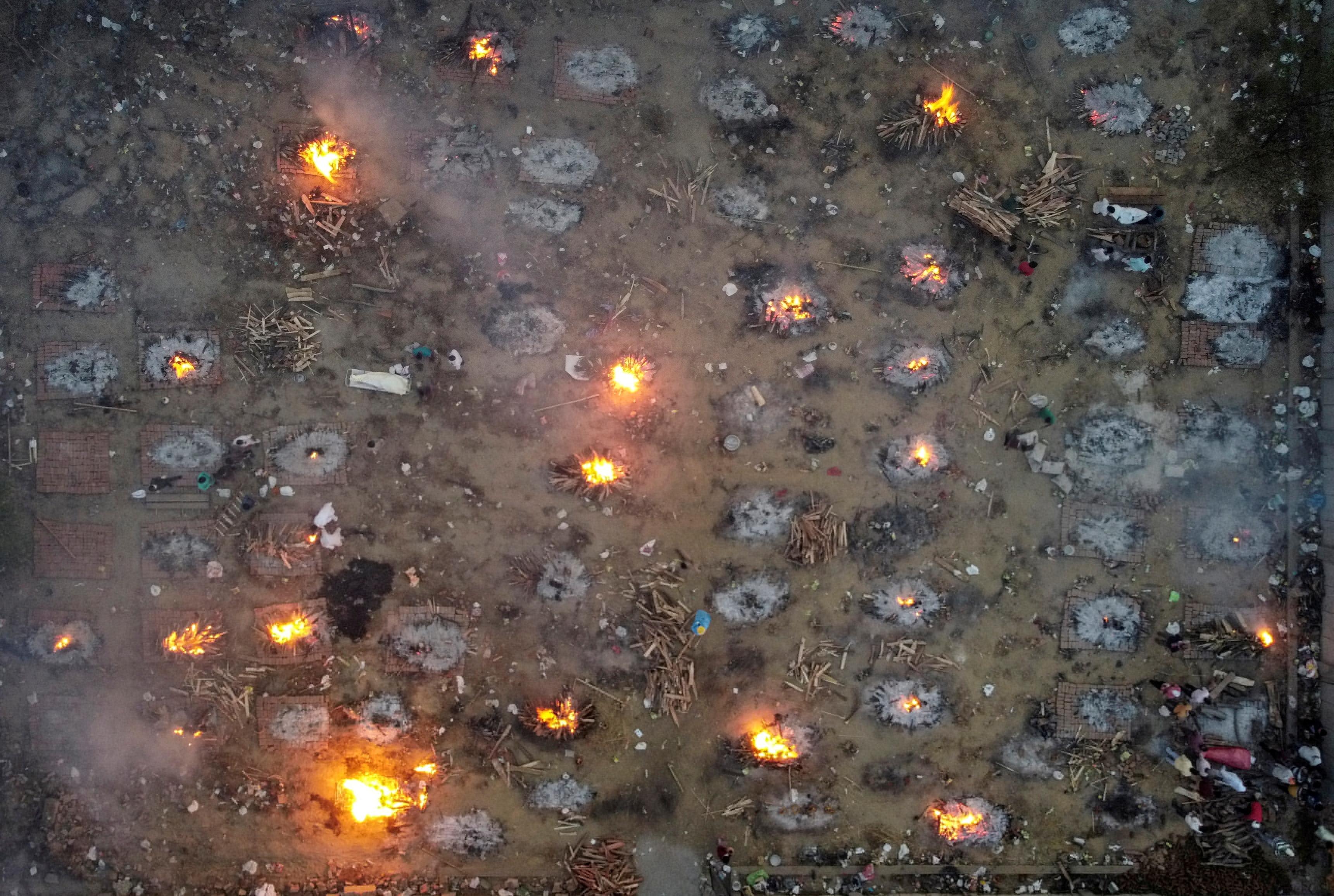 यह तस्वीर राजधानी दिल्ली की है। कोरोना की दूसरी लहर की पीक के दौरान जलती चिताओं की इस तस्वीर ने लोगों हिलाकर रख दिया था। (फोटो- रॉयटर्स)
