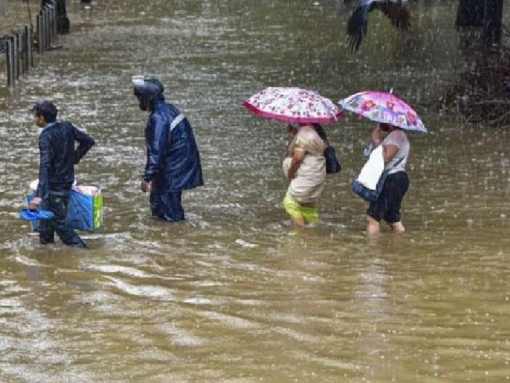 भारी बारिश के बीच ऑफिस जाते लोग कुछ मुंबईकर।