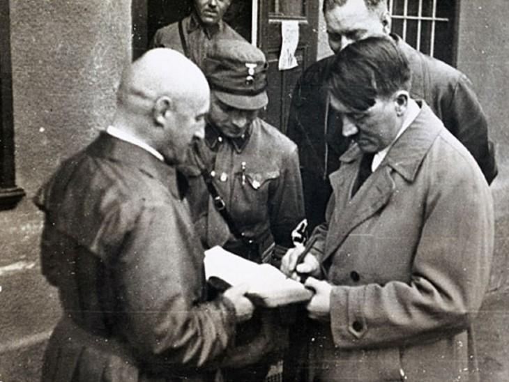 'माइन काम्फ' पर ऑटोग्राफ देते हुए हिटलर।
