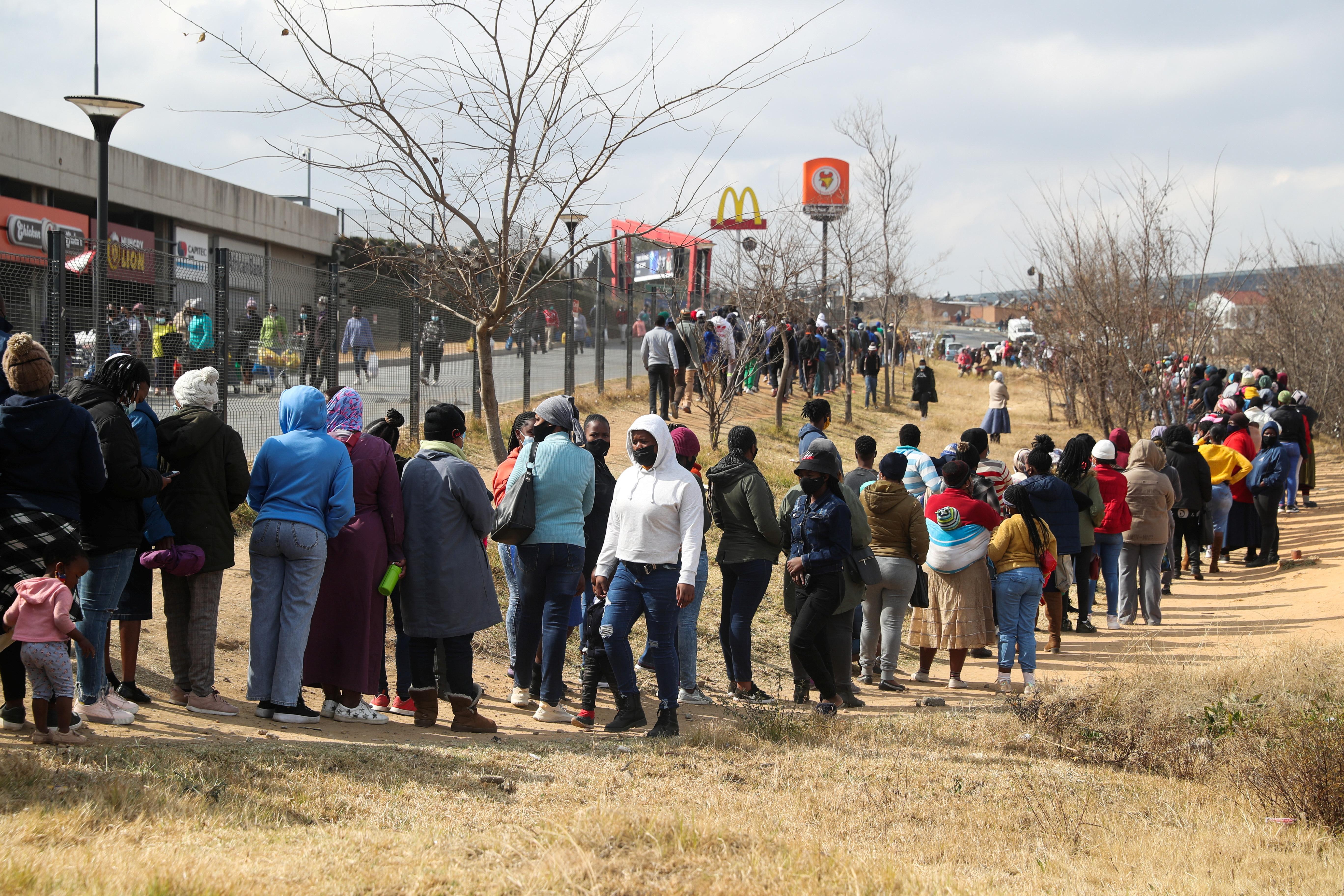 जाेहान्सबर्ग की अलेक्जैंड्रा टाउनशिप में एक मॉल को उपद्रवियों ने बख्श दिया। खाद्य सामग्री खरीदने के लिए उसी मॉल के बाहर लाइन में लगे लोग।