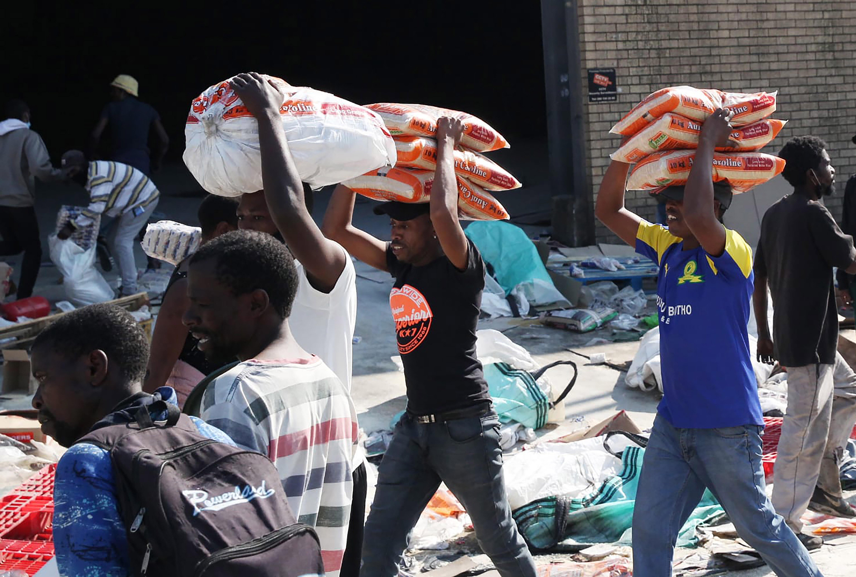 क्वाजुलू नाटाल प्रांत में हिंसा के बीच डरबन के मोबेनी में एक फैक्ट्री से चावल के पैकेट उठाकर ले जाते लोग।