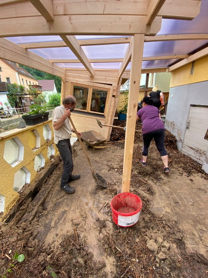 स्विट्जरलैंड के सैक्सन शहर में बारिश-बाढ़ से क्षतिग्रस्त घर से कीचड़ और मिट्टी निकालता परिवार।