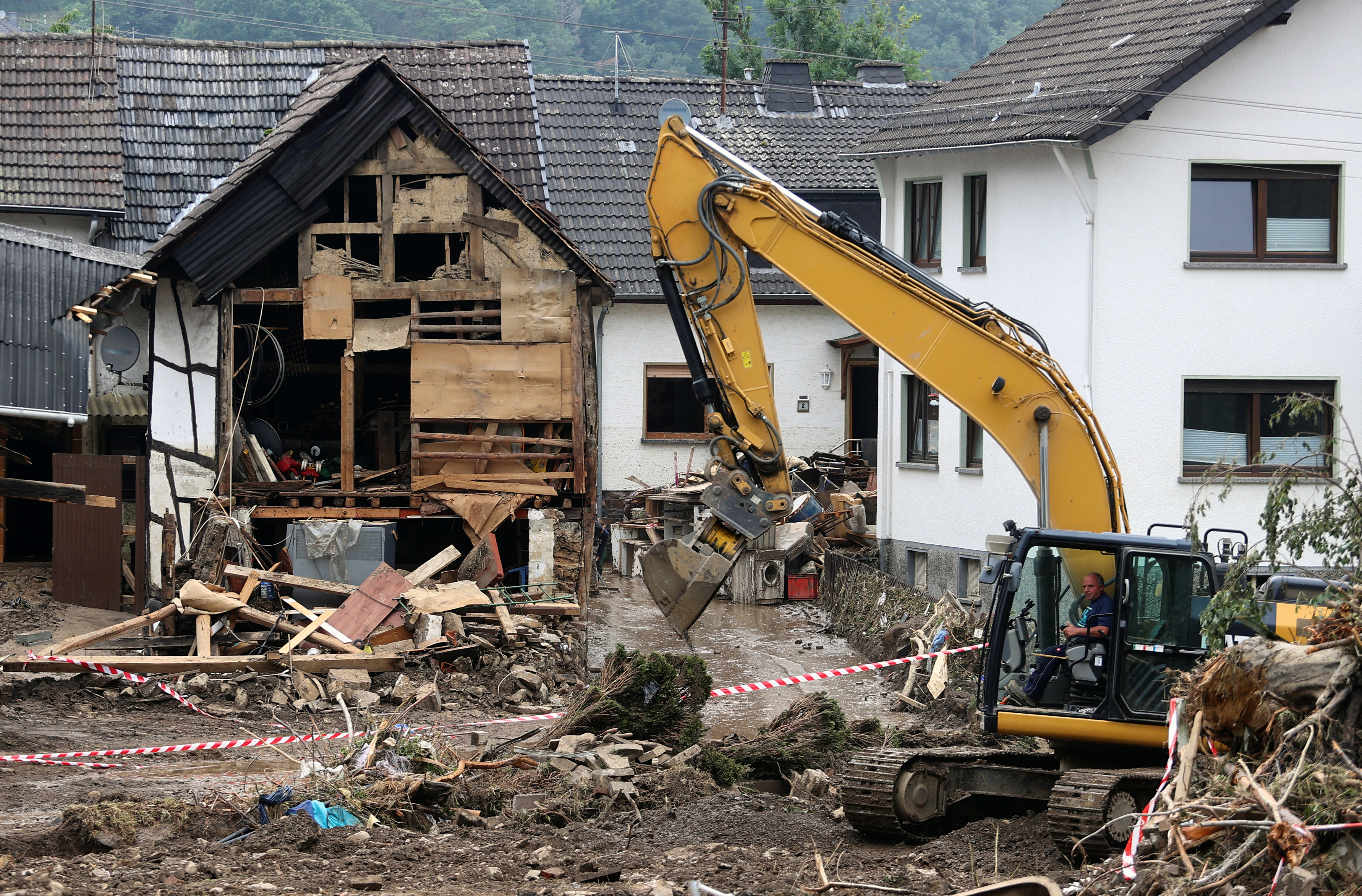 जर्मनी के शुल्ड गांव में बाढ़ से हुई तबाही के बाद जेसीबी से मलबा साफ करता कर्मचारी।