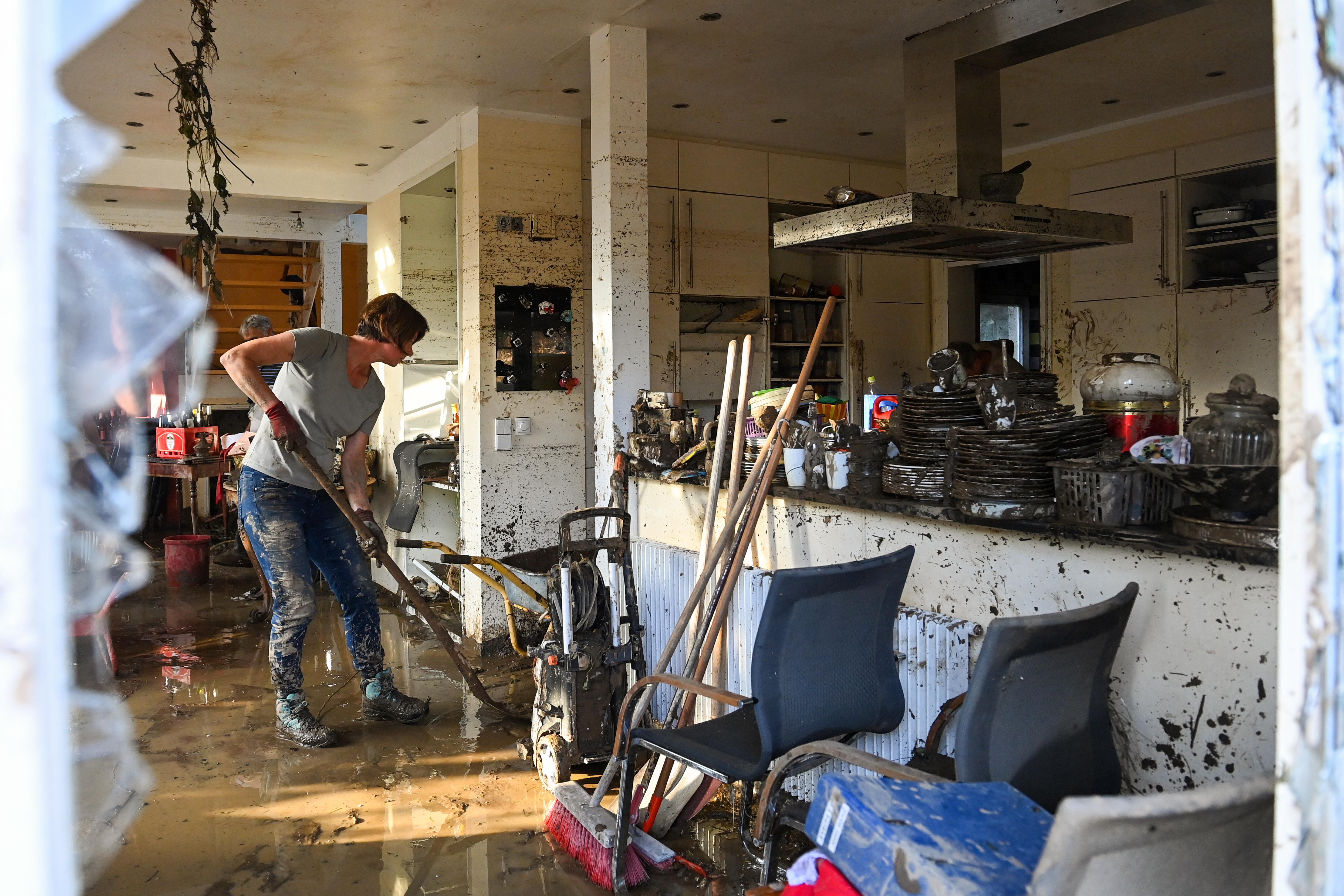 अहरवीलर इलाके में बुरी तरह से तहस-नहस घर को साफ करती महिला।