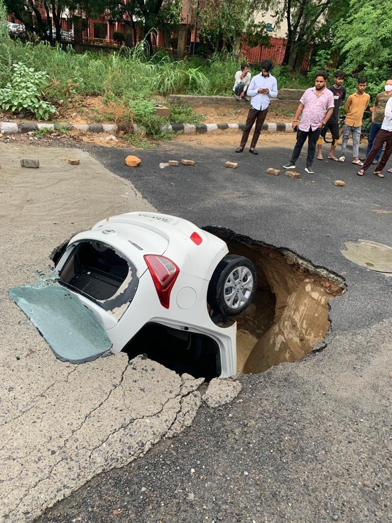 दिल्ली में द्वारका के सेक्टर-18 में सड़क धंसने से एक कार फंस गई। बाद में क्रेन की मदद से इसे बाहर निकाला गया।