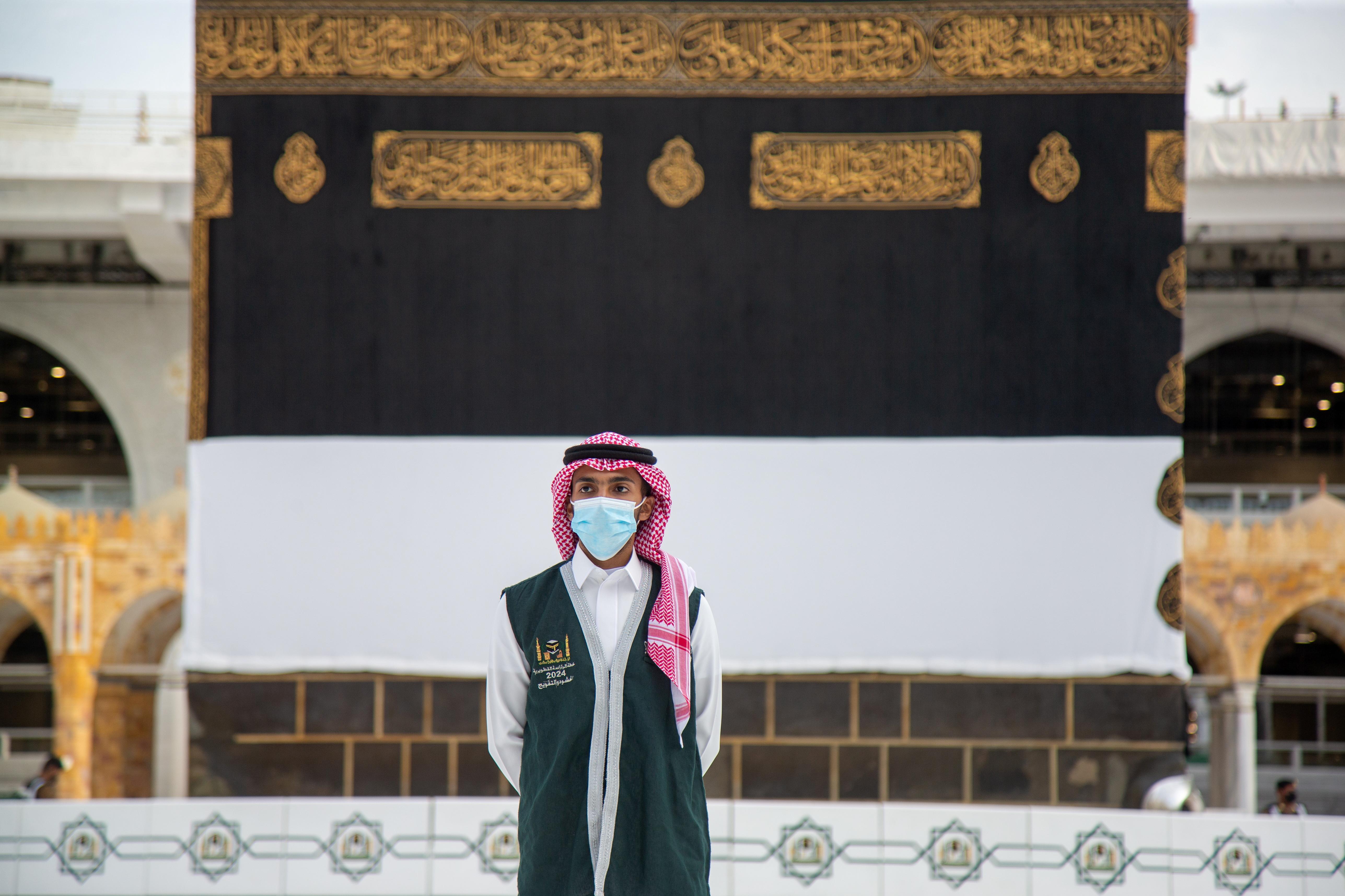 काबा के सामने मास्क पहन कर खड़े हज मंत्रालय के एक अधिकारी।