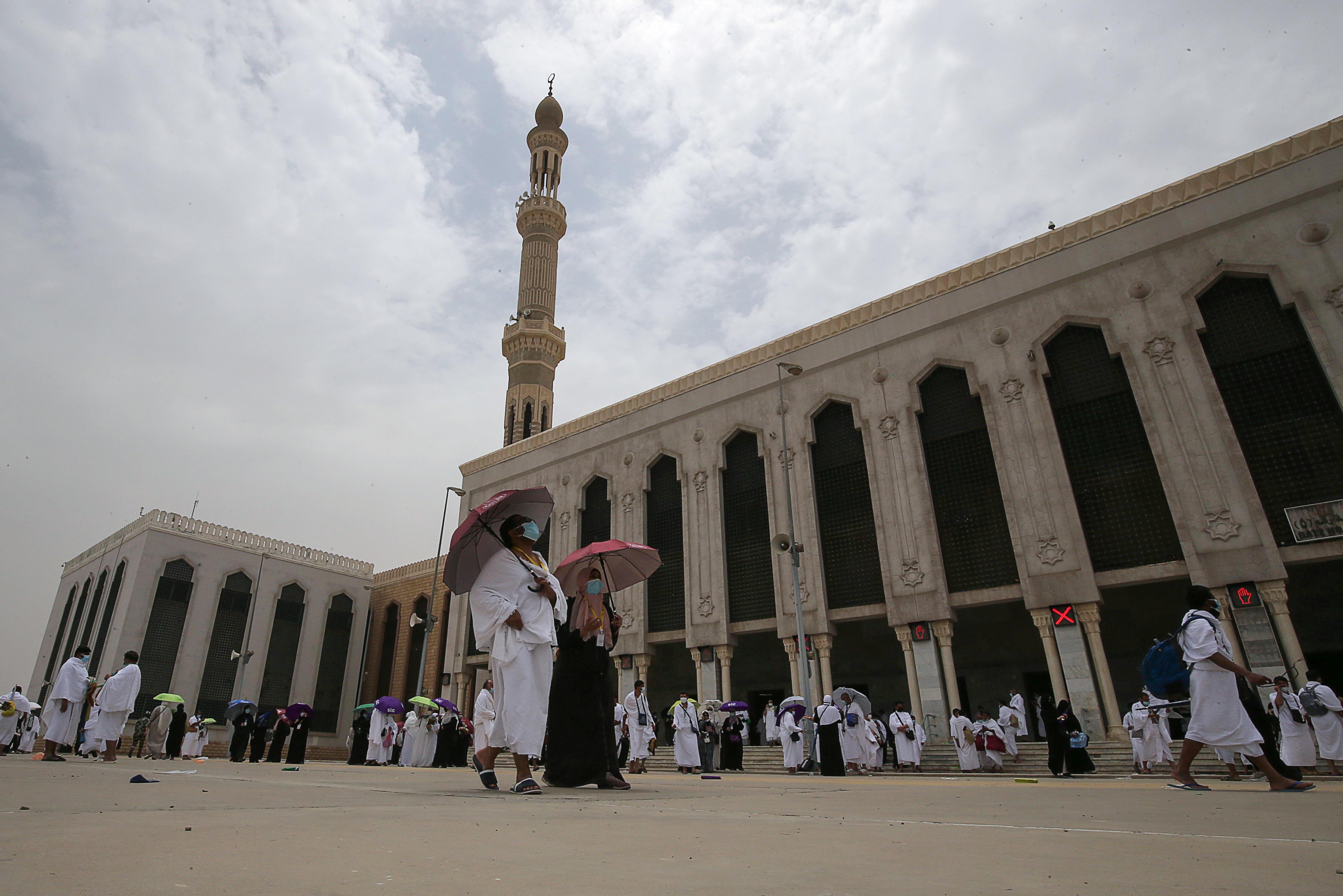 नमीरा मस्जिद के सामने से गुजरते हज यात्री। यहां हजारों लोग एक साथ नमाज पढ़ते हैं।