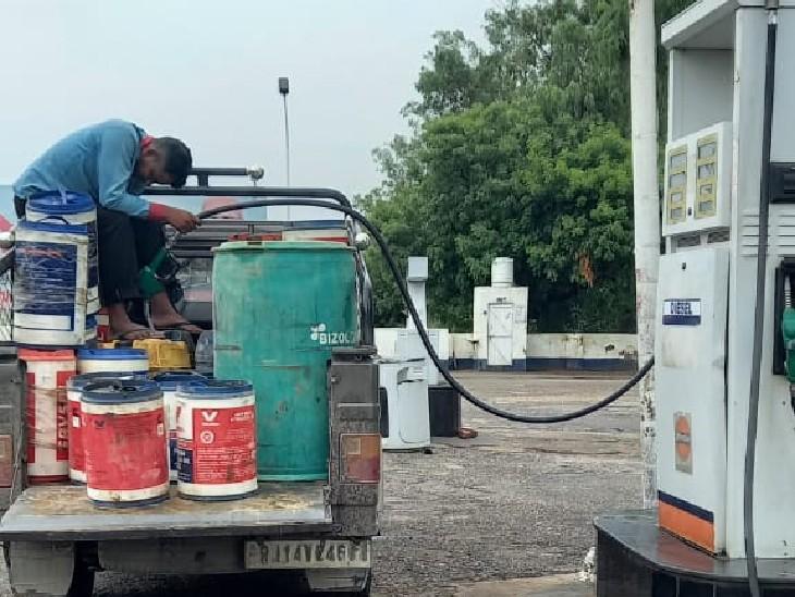 राजस्थान की गाड़ियों में रखे ड्रम में डीजल भरता यूपी पेट्रोल पंप का कर्मचारी।