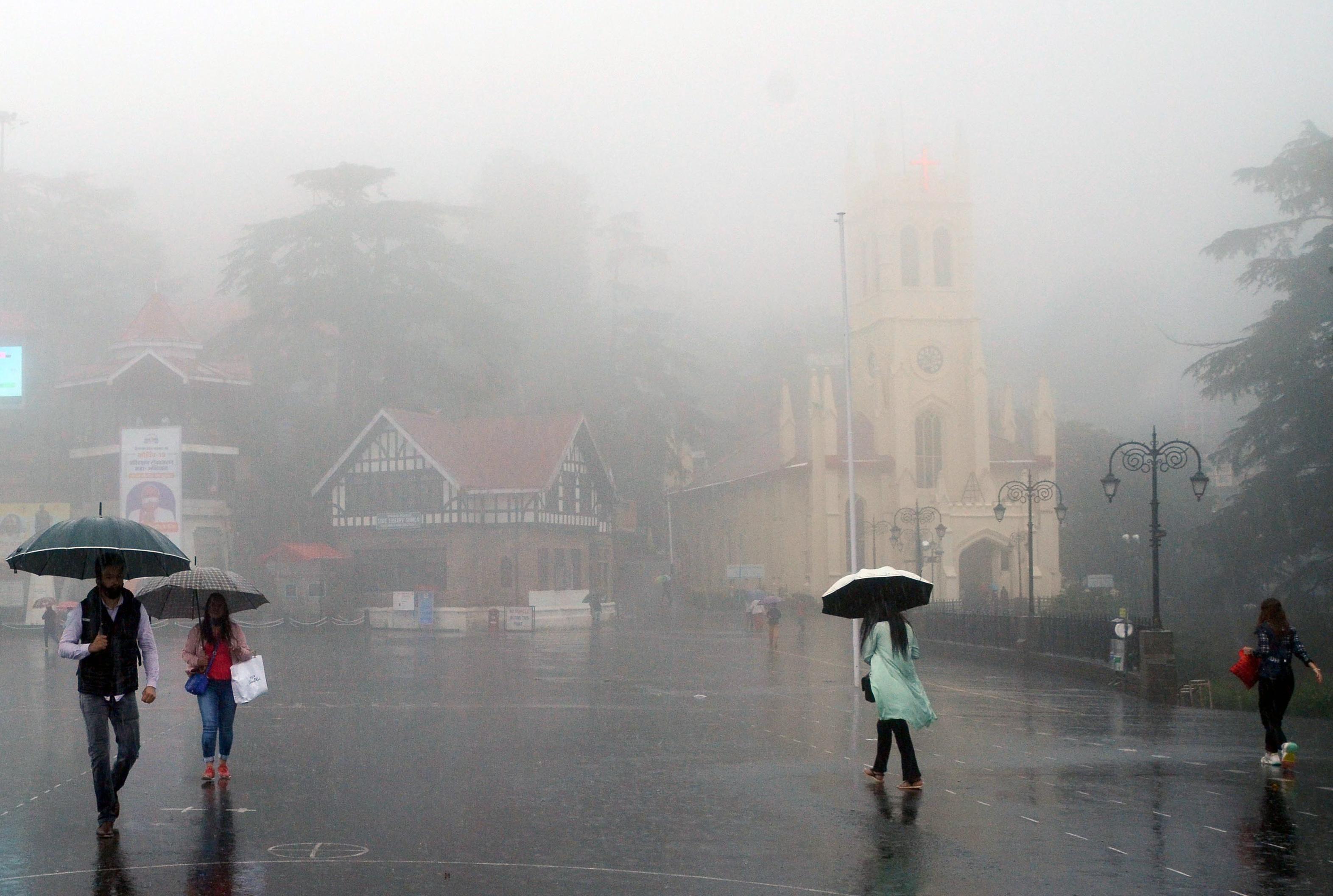 सोमवार को शिमला में हुई जोरदार बारिश में निकले लोग।