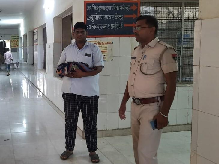 नवताज को पुलिसकर्मी इस तरह गोद में लिए खड़ा रहा।
