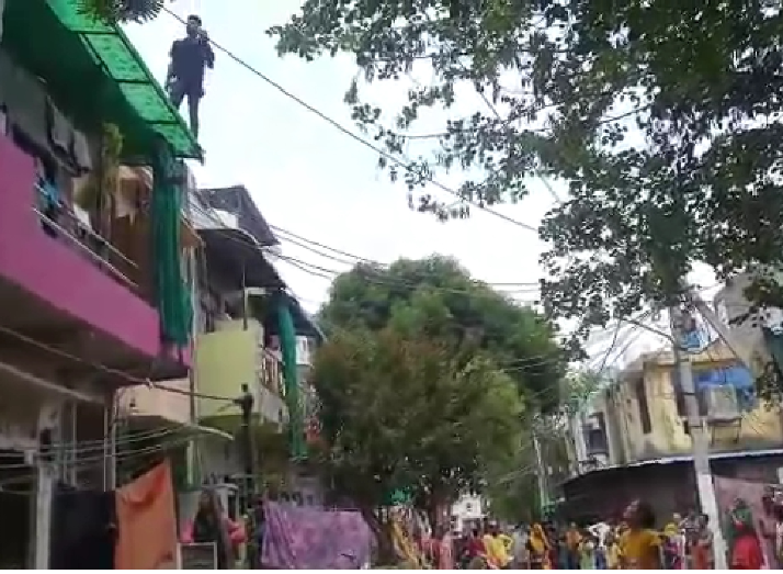 पुलिस से बचने के लिए एक युवक घर की छत पर चढ़ गया