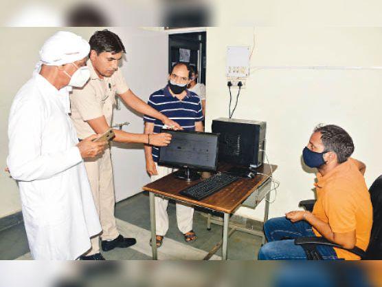 बुजुर्ग को सिस्टम पर वैक्सीन खत्म के बारे में दिखाता सुरक्षाकर्मी। - Dainik Bhaskar