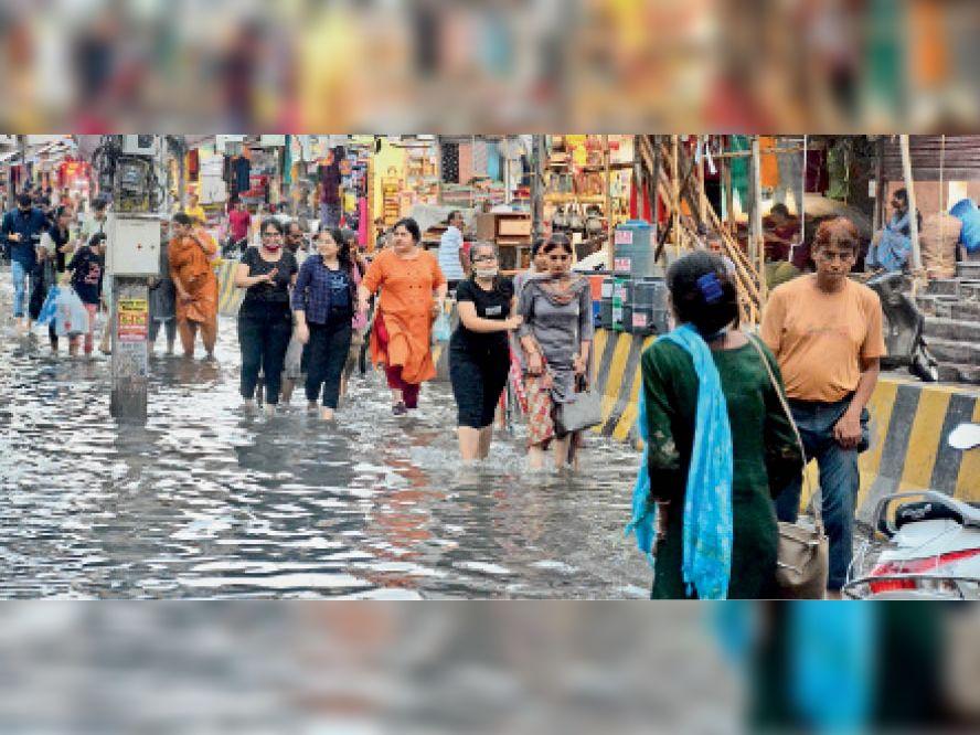राेहतक.किला राेड बाजार में भरे हुए बरसात के पानी के बीच से गुजरती हुई महिला। - Dainik Bhaskar