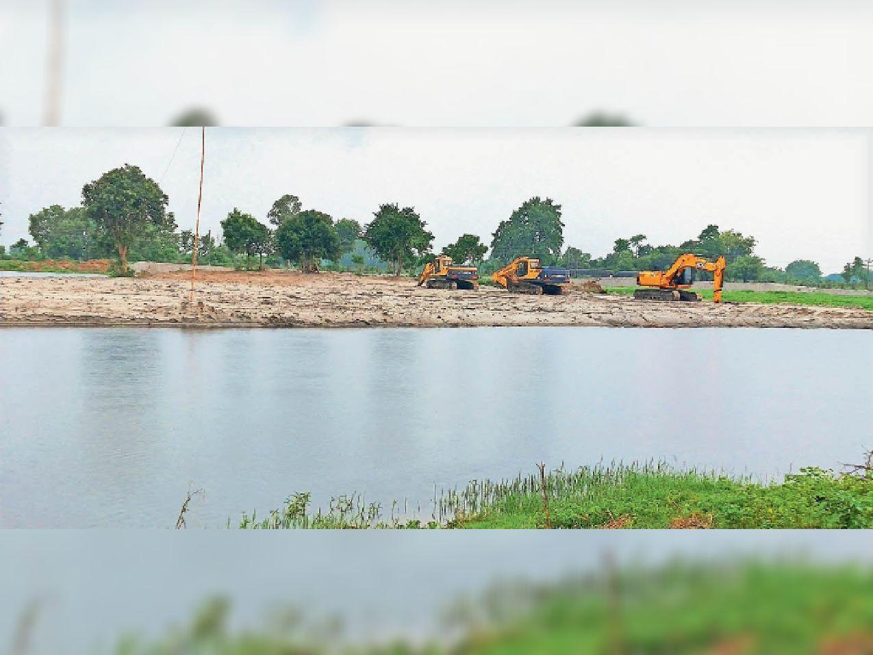 पानी बढ़ने के कारण कार्य बंद कर खड़ी जेसीबी। - Dainik Bhaskar