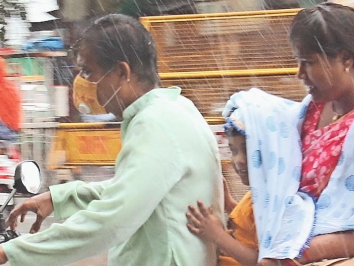 माता-पिता के साथ बाइक पर जाता बच्चा बूंदों के कारण मुस्कुराता हुआ। - Dainik Bhaskar