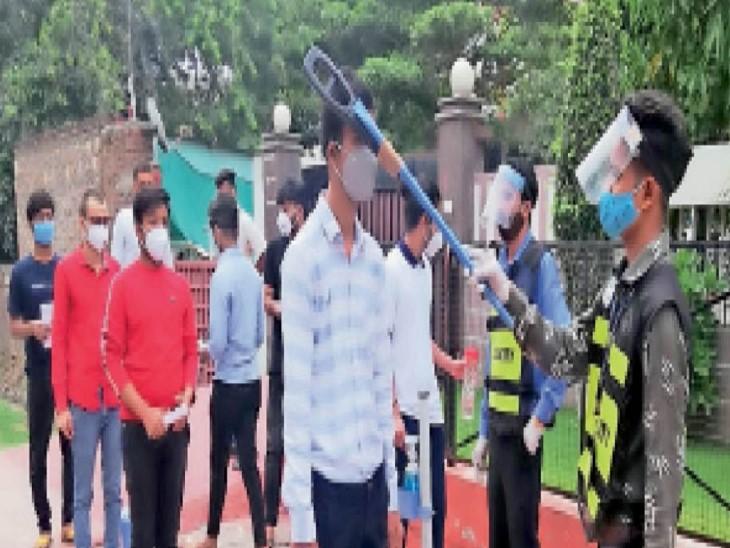 परीक्षा केंद्र पर छात्र-छात्राओं की जांच करते हुए कर्मचारी। - Dainik Bhaskar