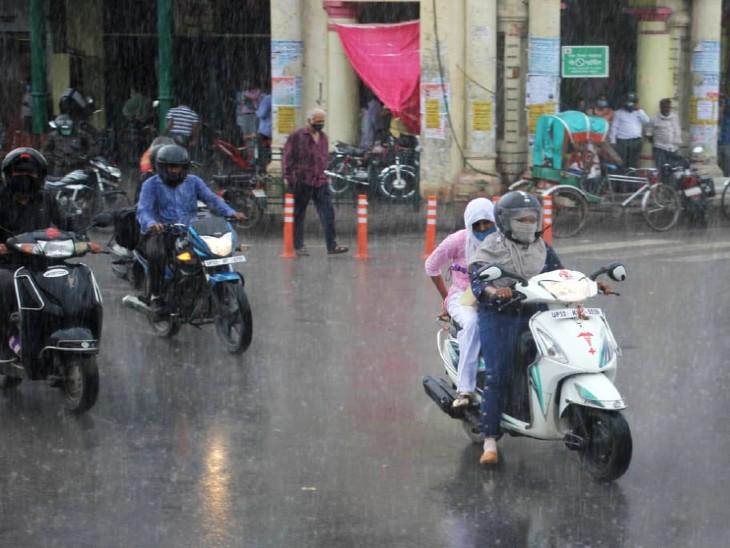 लखनऊ: बारिश के बीच अपने काम पर जाते लोग।