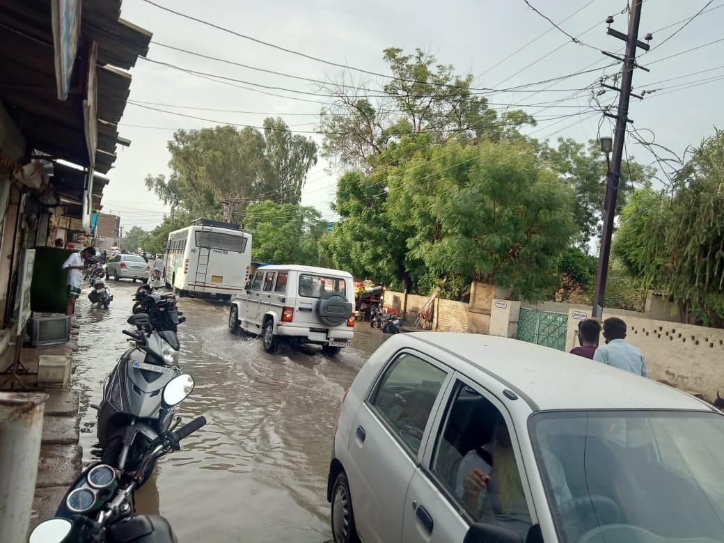 रायसिंहनगर में सड़क  पर जमा पानी से गुजरते वाहन। - Dainik Bhaskar