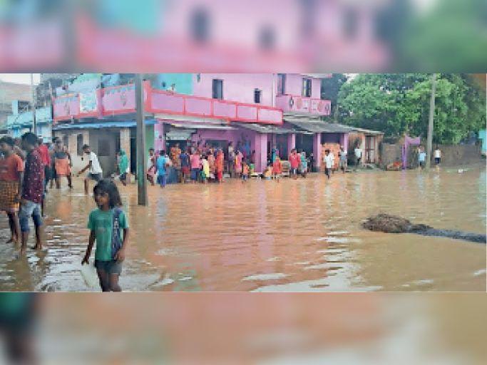 बाढ़ का पानी गांव में चढ़ने के बाद घर से बाहर निकले लोग। - Dainik Bhaskar