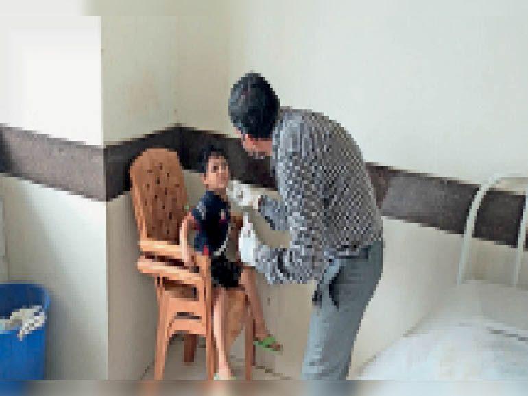 जिला अस्पताल में बच्चे का सैंपल लेते स्वास्थ्य कर्मी। - Dainik Bhaskar