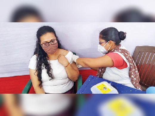 कोरोना का टीका लगवाती युवती। - Dainik Bhaskar