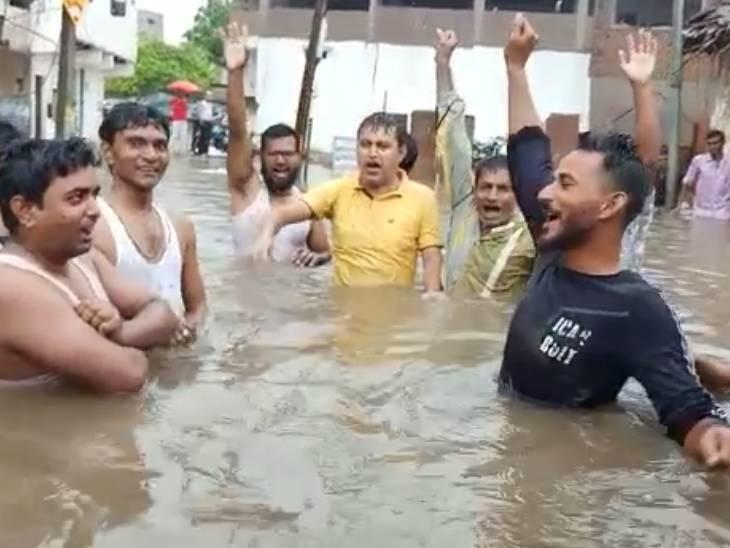 नगर पालिका के खिला पानी में खड़े लोग नारेबाजी करते हुए।