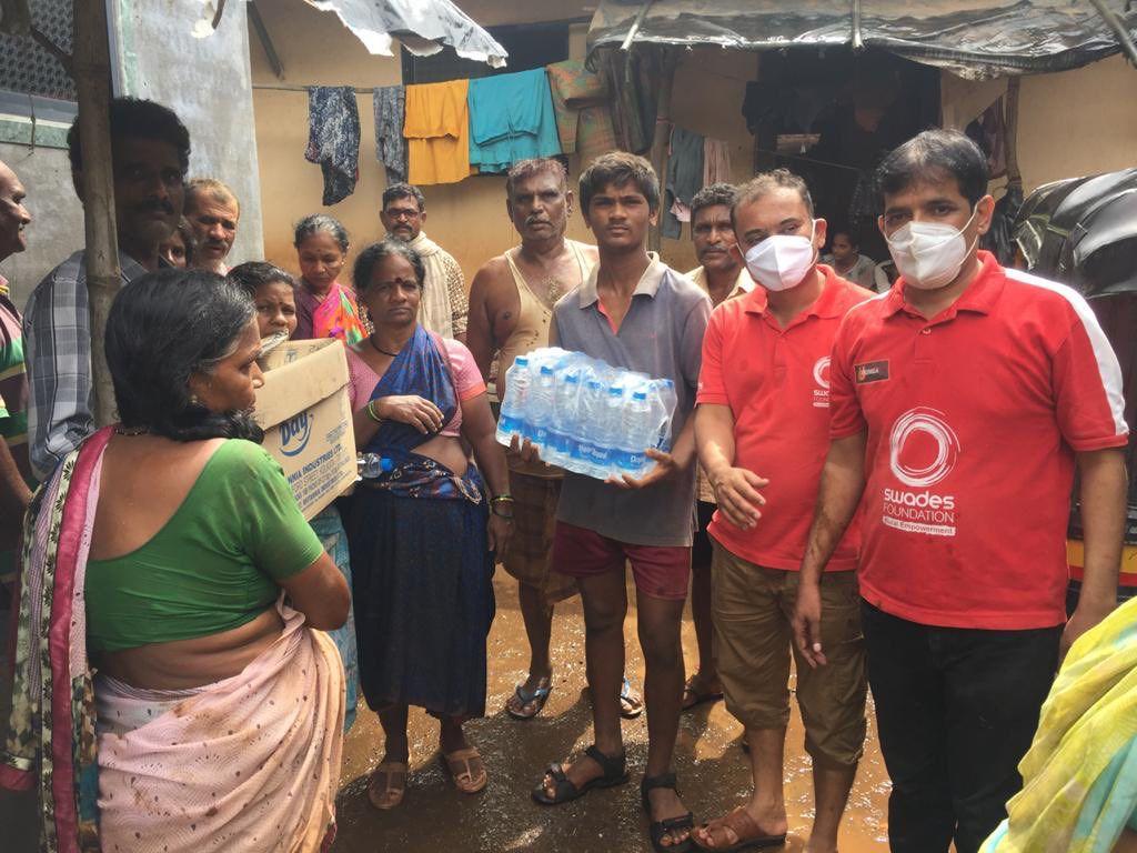 गांव के लोगों को राहत सामग्री बांटते सामाजिक कार्यकर्ता।