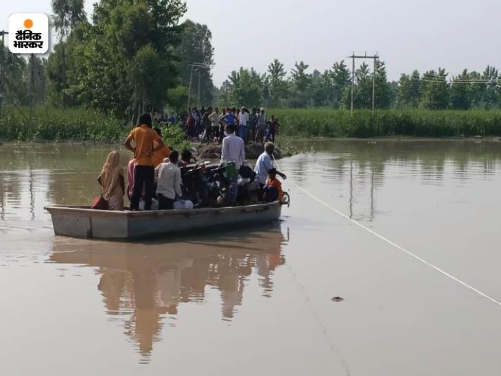 नाव पर ही बाइक और ग्रामीण एक साथ नहर को पार कर रहे हैं।
