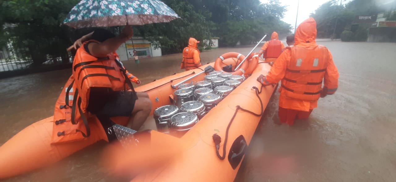 कोल्हापुर में सड़कें बारिश के पानी में डूब गई हैं। इस बीच लोगों तक खाना पहुंचाते NDRF के जवान।