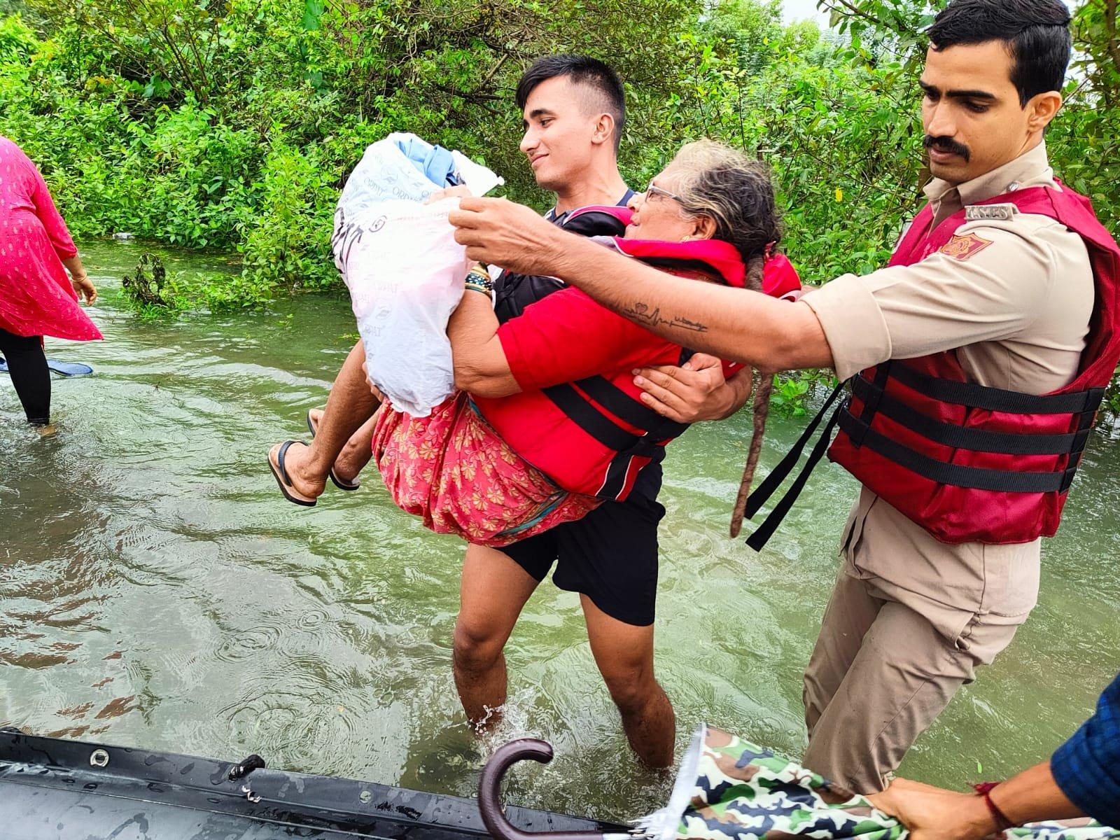 गोवा के कई जिलों में भारी बारिश के बाद बाढ़ जैसे हालात हैं। फोटो में एक बुजुर्ग महिला को उठाकर नाव तक पहुंचाता NDRF का जवान।