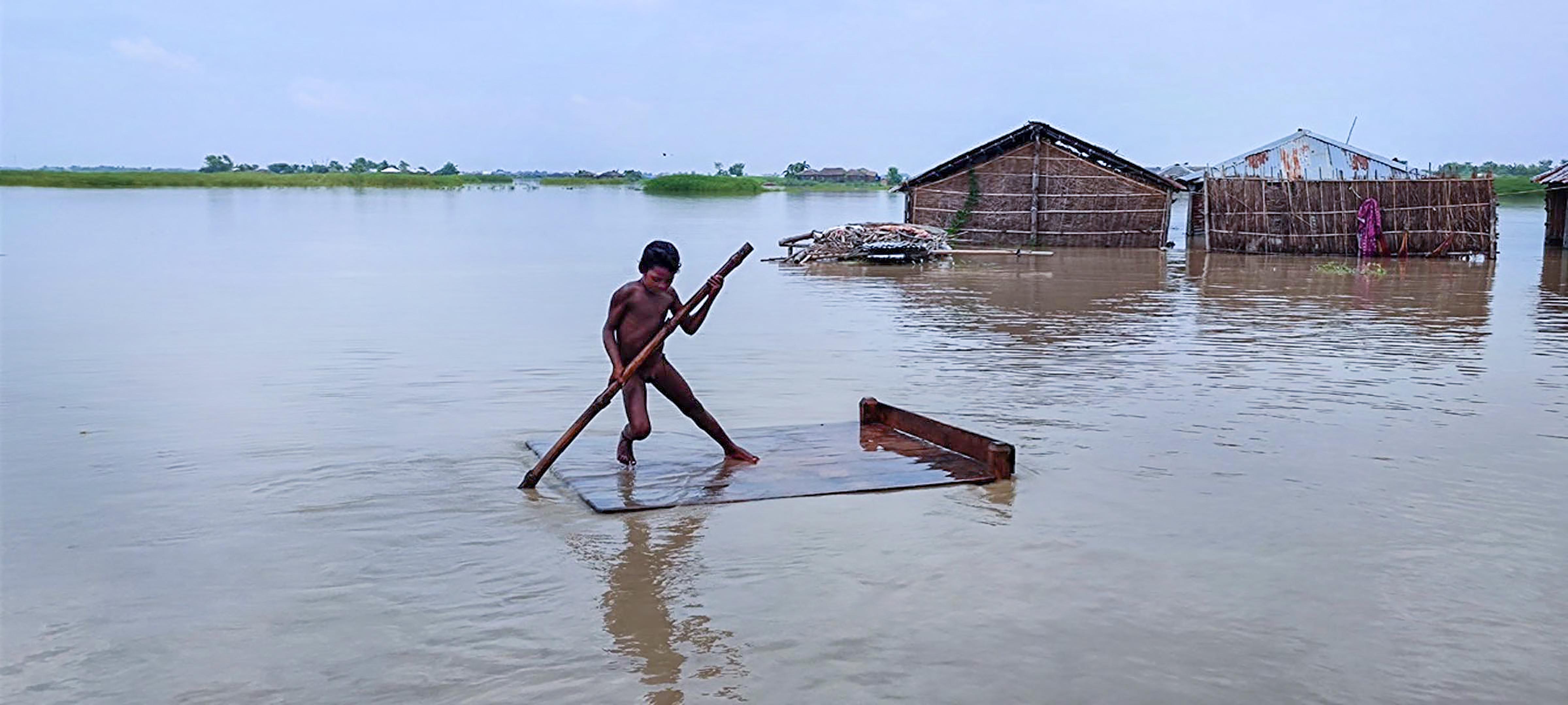 बिहार के सहरसा जिले के कई गांव बाढ़ की चपेट में हैं। बाढ़-पानी के बीच लकड़ी के पटिये पर सवार बच्चा।