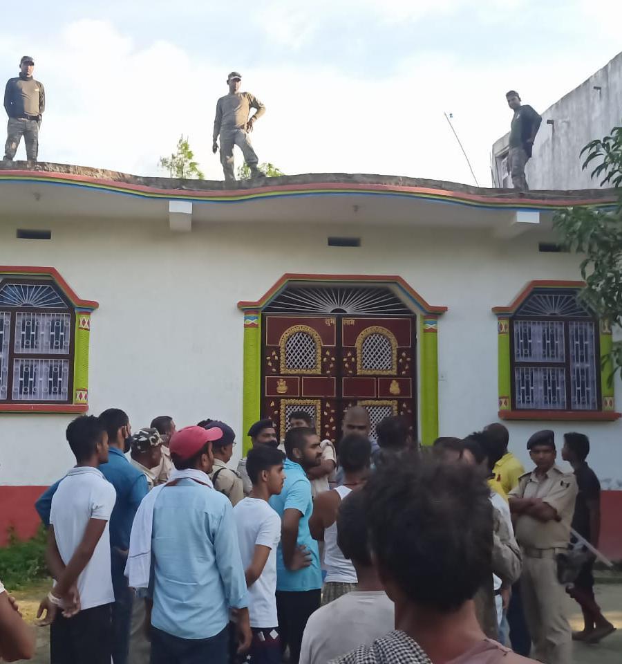 आरोपी के घर के गेट पर इकट्ठा भीड़ और छत पर खड़े होकर पहरेदारी करते पुलिसकर्मी।