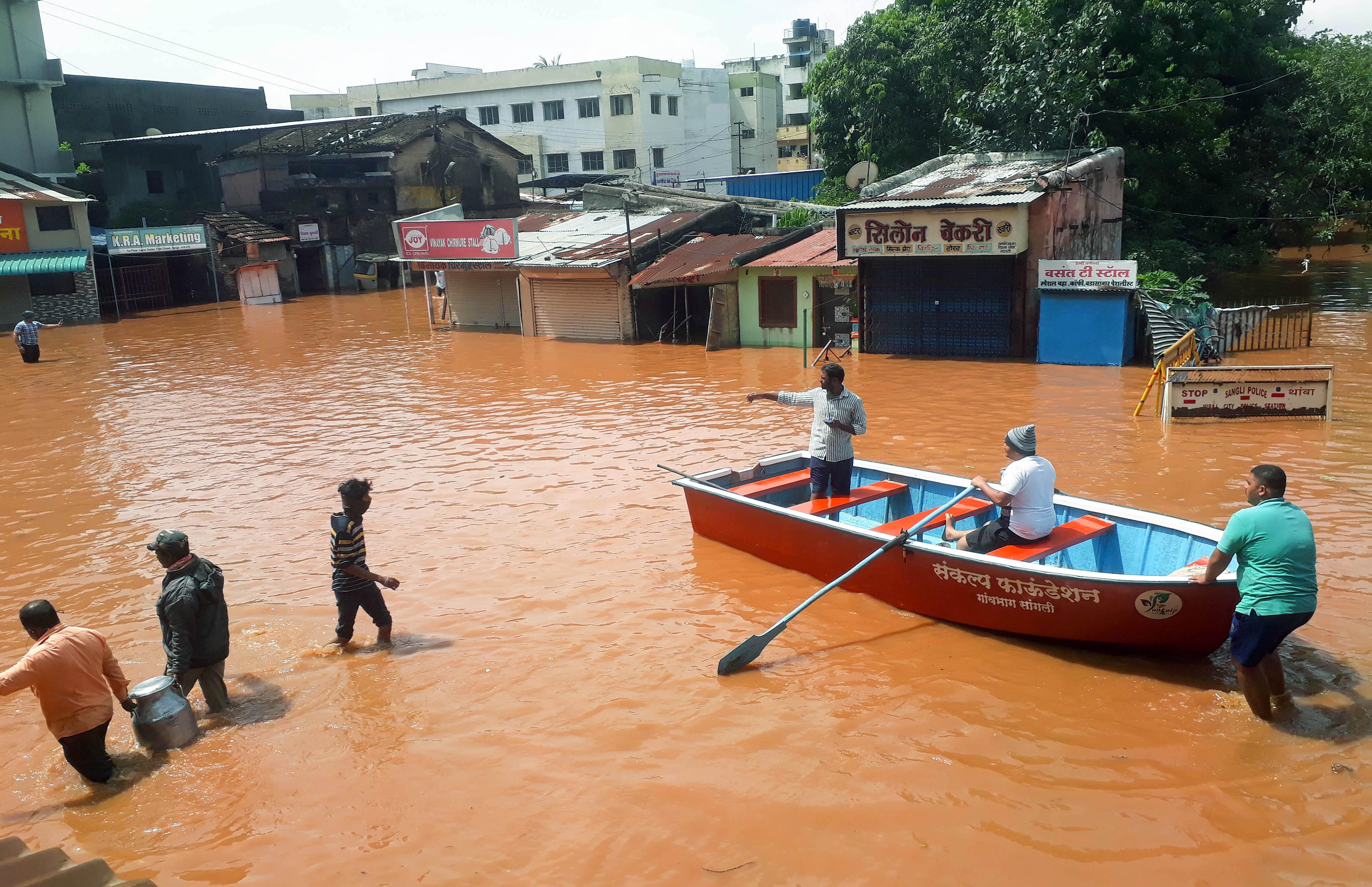 कृष्णा नदी के उफनने से सांग्ली जिले के इलाकों में बाढ़ से लोगों को बचाते स्थानीय कार्यकर्ता।